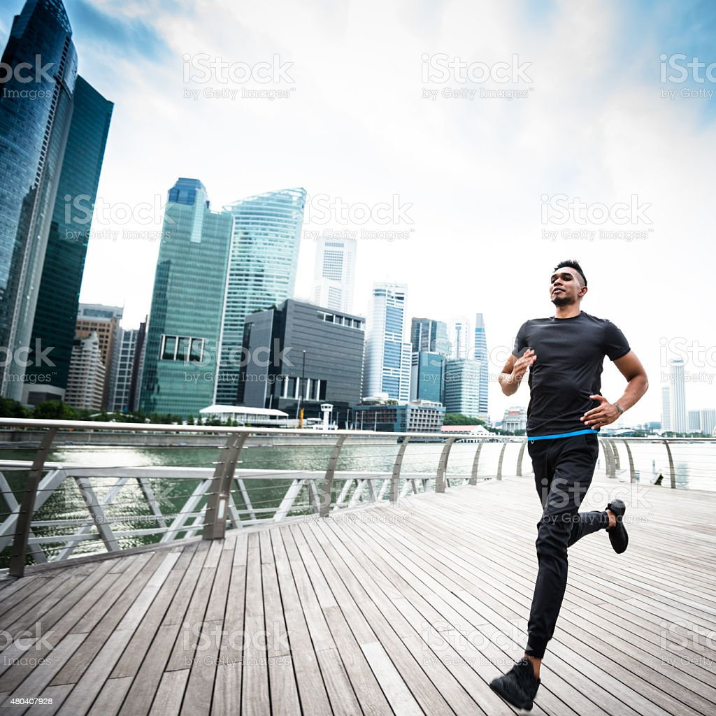 man running on the city of singapore marina bay area stock photo