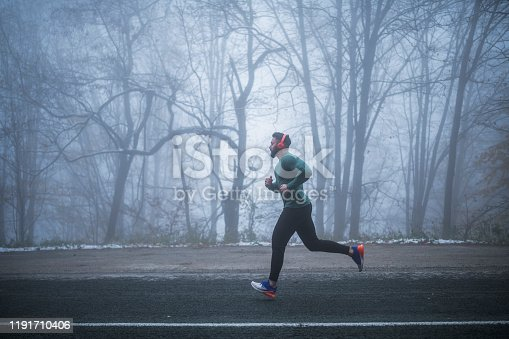 Full length man wearing sports clothing and red headphones running on the road in foggy weather condition.