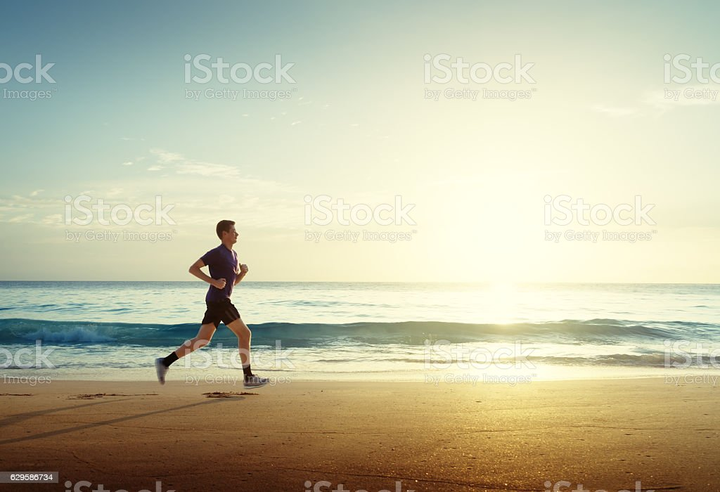 Man running on tropical beach at sunset royalty-free stock photo