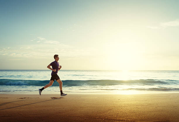 man running on tropical beach at sunset - jogging stock pictures, royalty-free photos & images