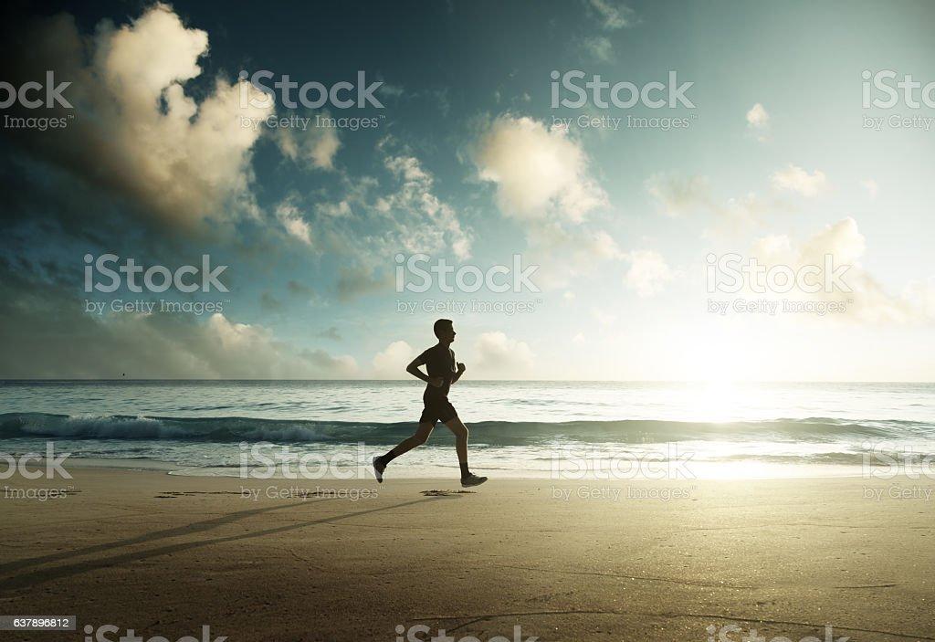 Man running on tropical beach at sunset stock photo