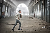 Side View of Young Man Running Through Abandoned Arched Tunnel