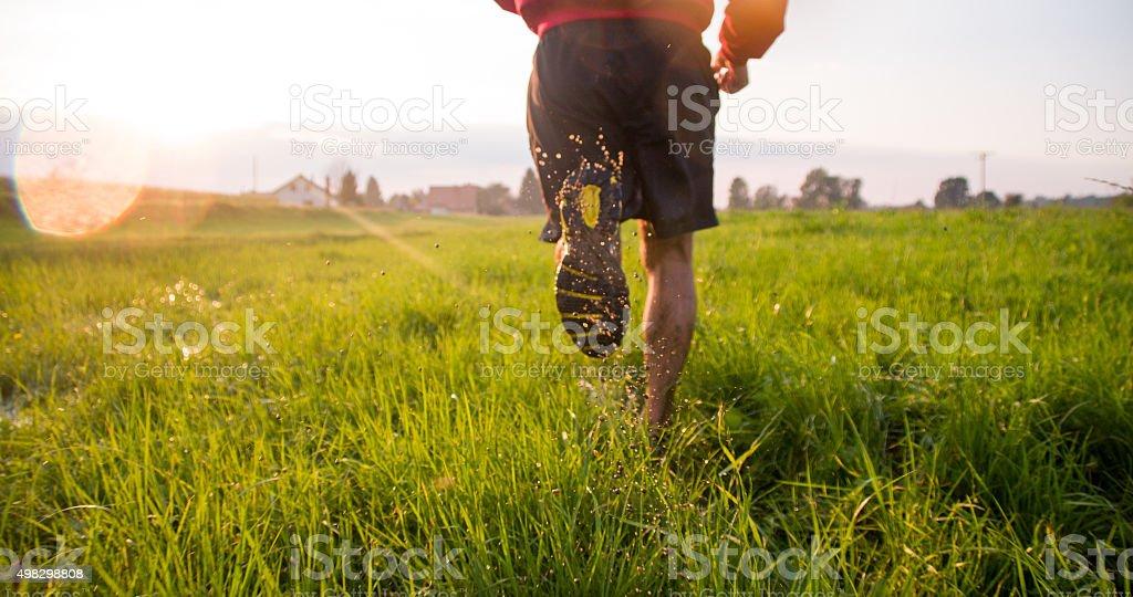 Man Running Through Wet Grass stock photo