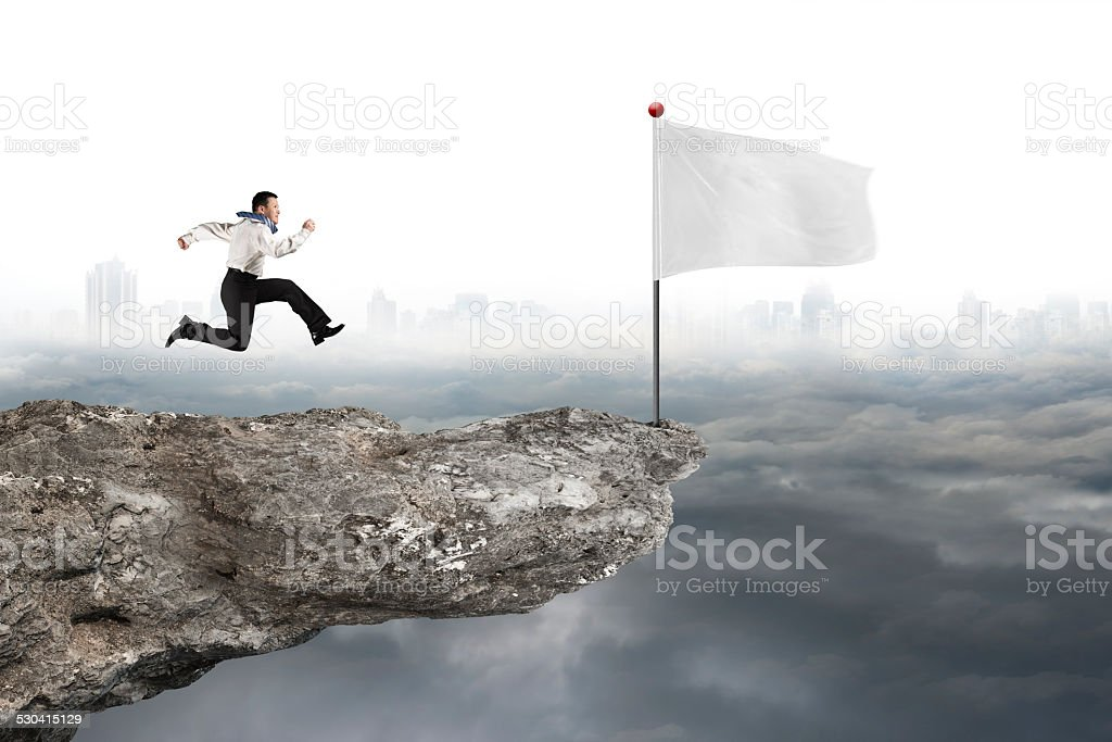 man running to white flag on cliff with cloudy cityscape stock photo
