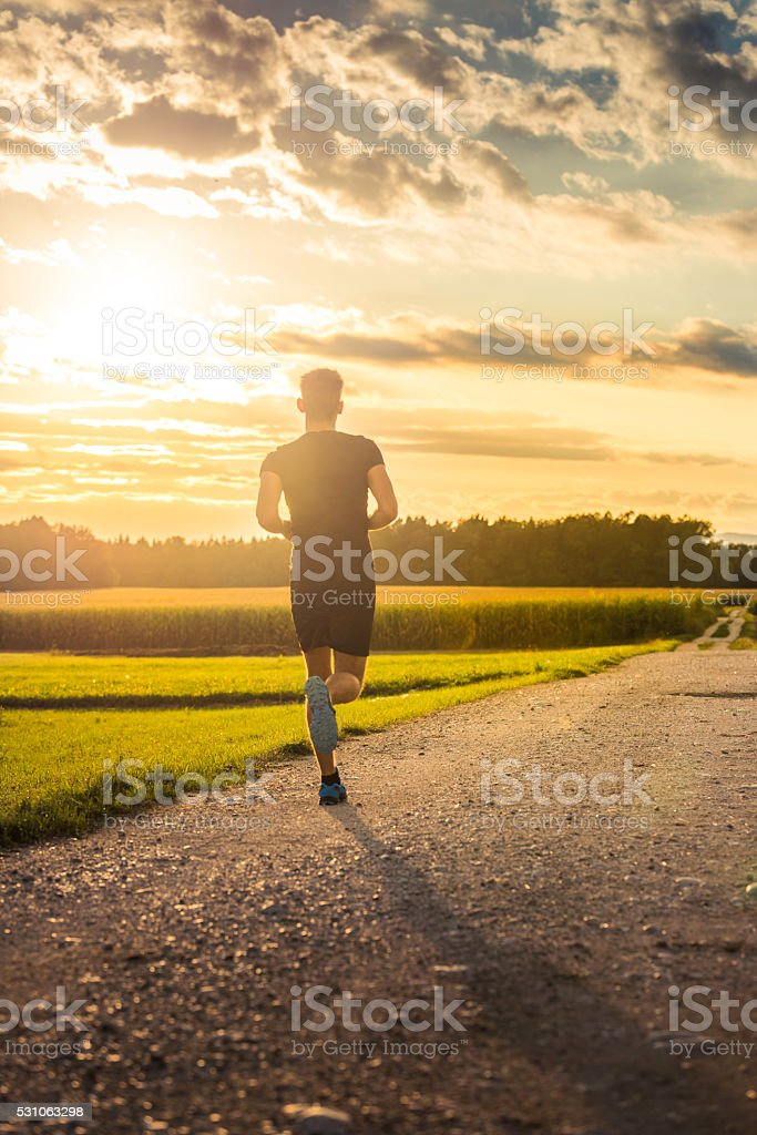 Man running towards sunset stock photo