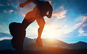Man running towards the sunset in the mountains. Outdoor activities. Exercising and workout.