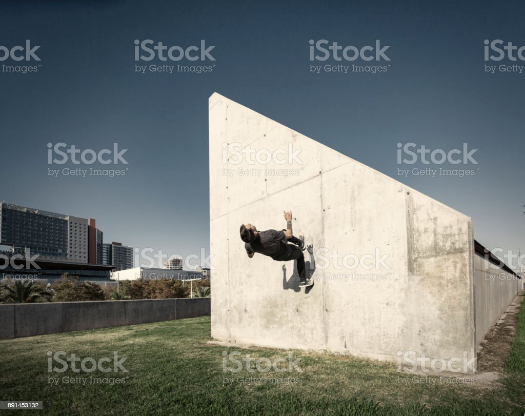 Man running up wall while practicing parkour in the city stock photo