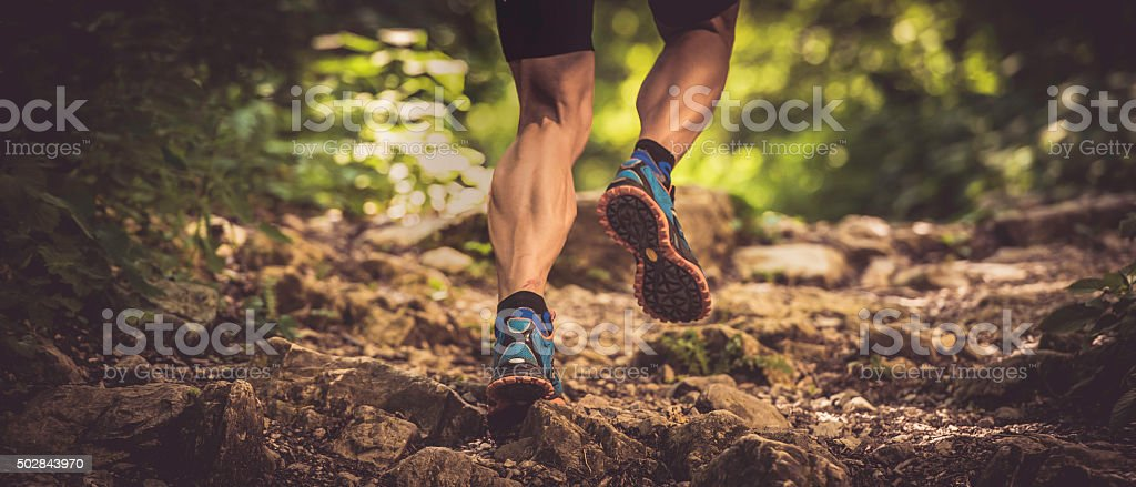 Man running uphill on a rocky forest path stock photo