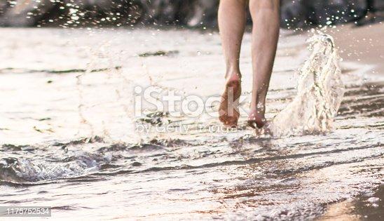 174919648 istock photo Man running  walking barefoot along beach 1175752534
