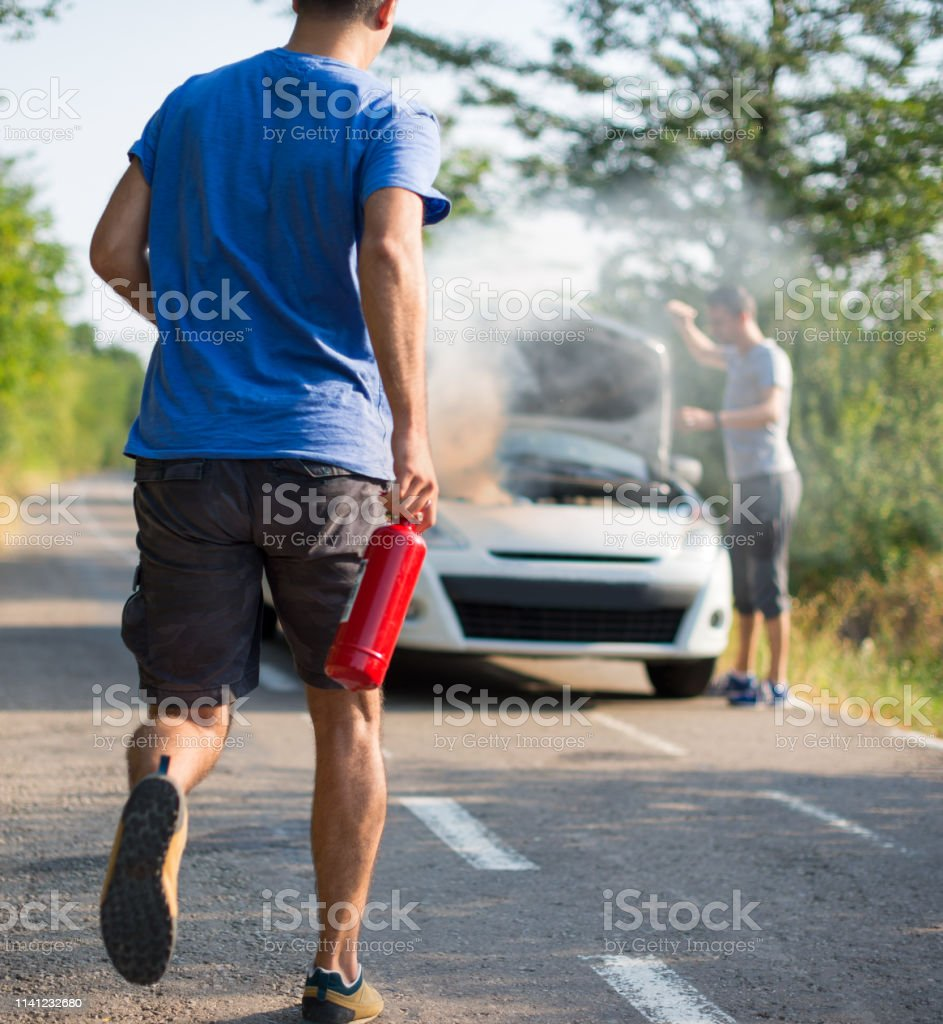 Man running with a car extinguisher to help another driver to...