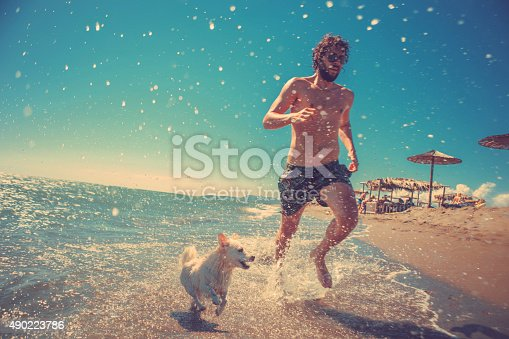 full body shot of young man running with his dog on the beach