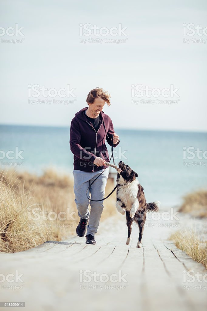 Man running with his dog stock photo