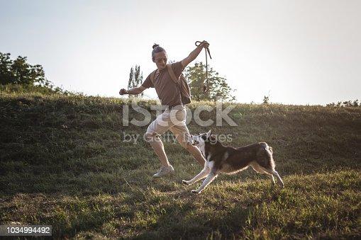 Man running with husky dog