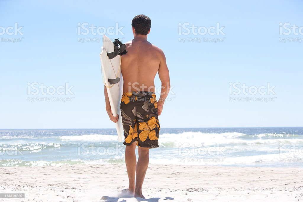 Man running with surfboard on beach royalty-free stock photo