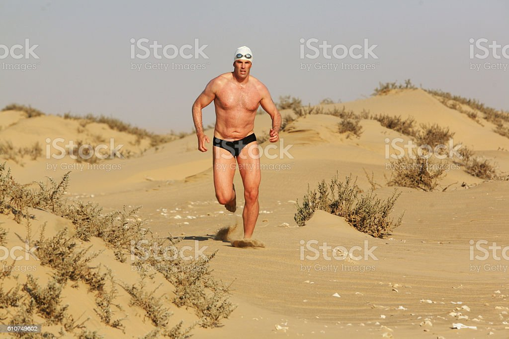 Man runs along dune with scrubby plants stock photo