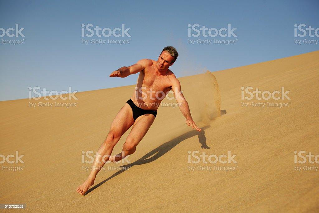 Man runs down a dune stock photo