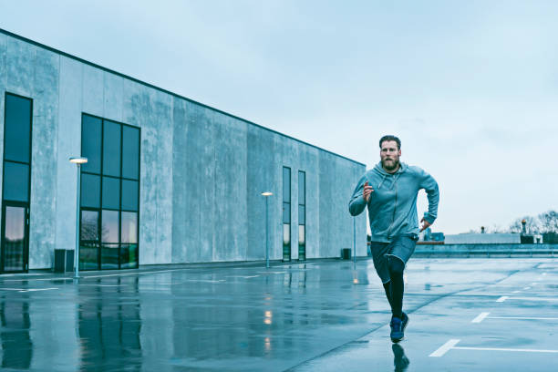Man runs fast outside and the sky is grey stock photo