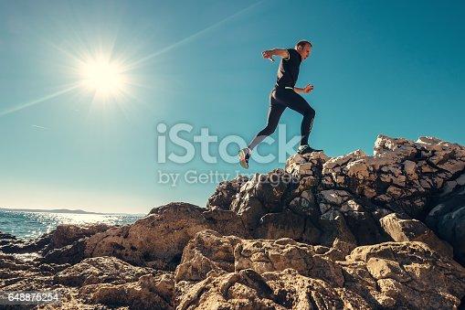 istock Man runs on rocky sea side 648875254