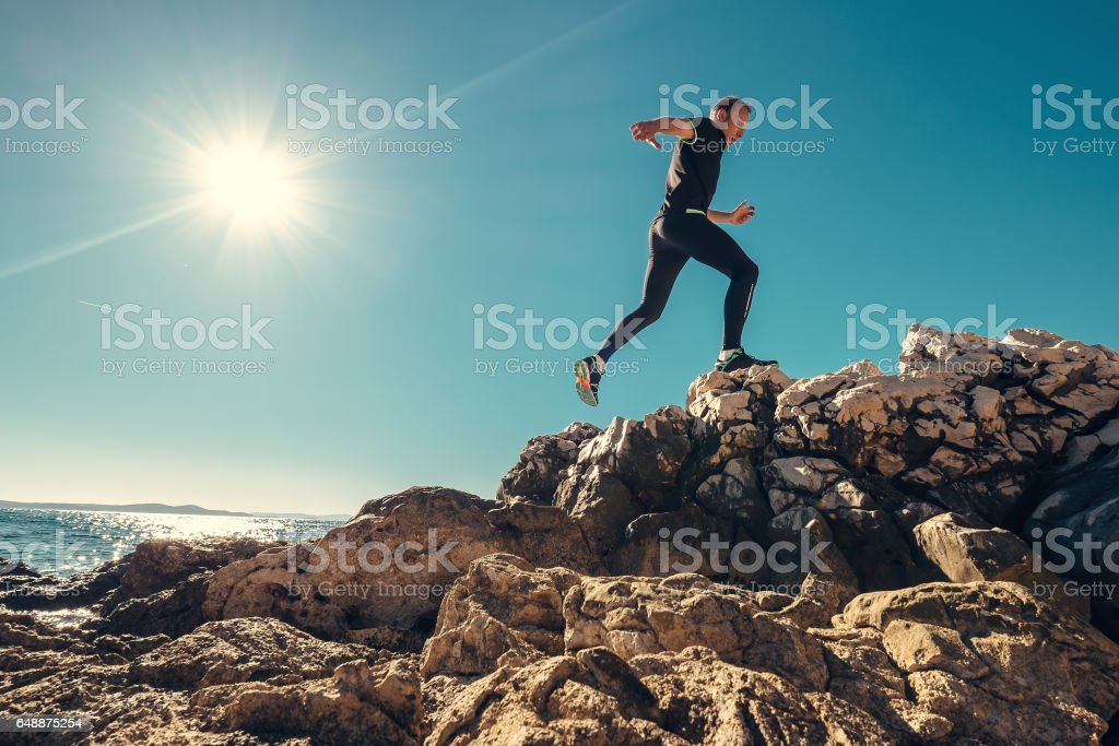 Man runs on rocky sea side stock photo