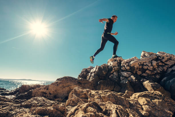 man runs on rocky sea side - athlete stock photos and pictures