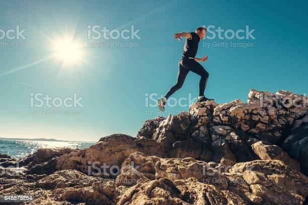 Photo of Man runs on rocky sea side