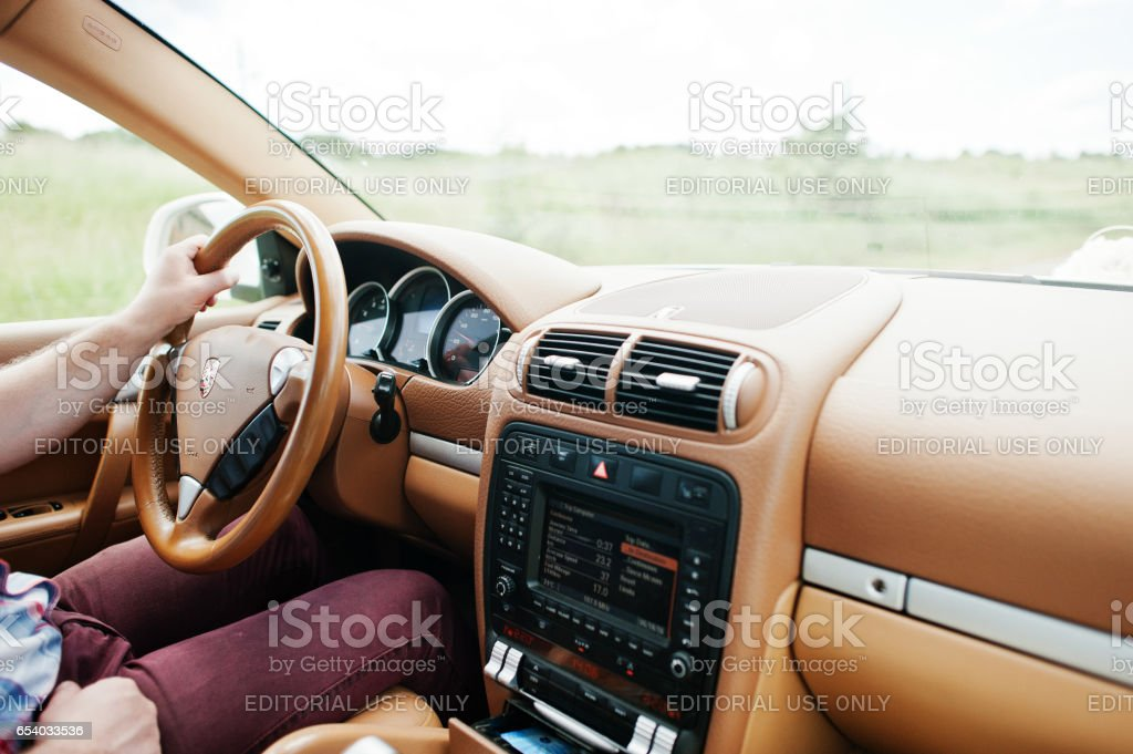 Man runs Porsche Cayenne car Hai, Ukraine - October 20, 2016: Man runs Porsche Cayenne car Adult Stock Photo