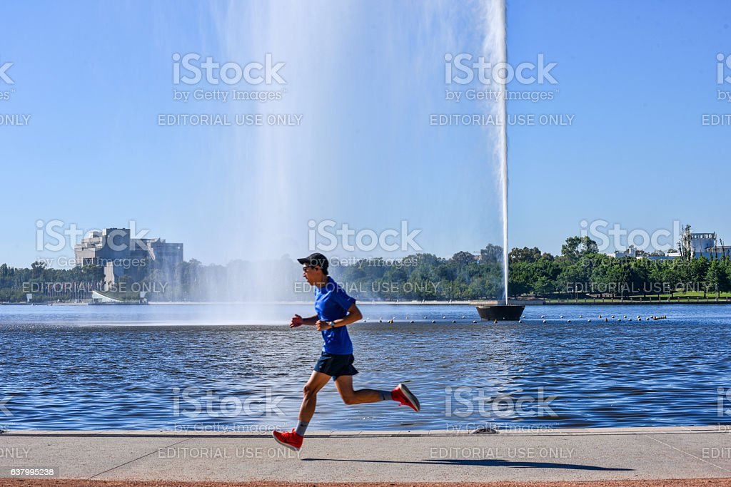 Man runs round the lake near the water jet, Canberra stock photo