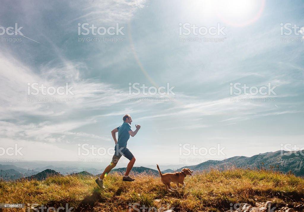 Mann fährt mit seinem Hund Beagle auf Berggipfel – Foto