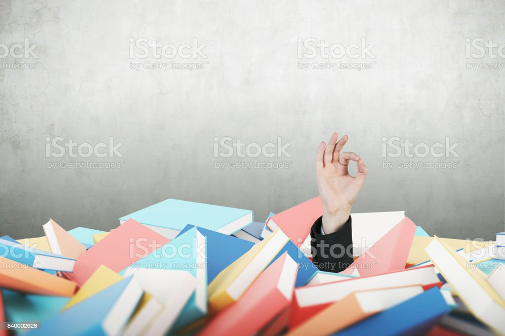 Man s hand making ok sign, pile of books stock photo
