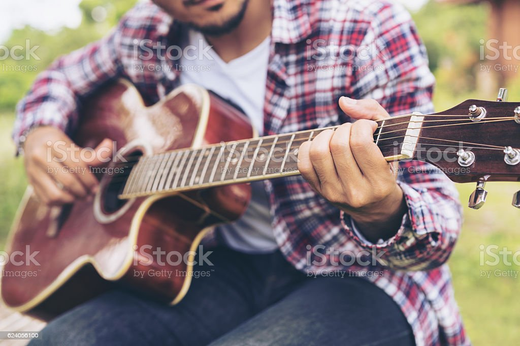 Man 's hand playing guitar, sitting on green grass stock photo