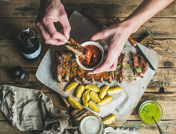 man' s hands dipping piece of roasted pork to ketchup - rib voedsel stockfoto's en -beelden