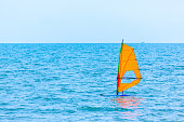 Man sailing a orange windsurf, the recreational surface water sport in the blue sea during summer vacation.