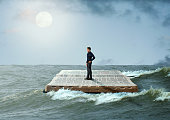 man sailing on the Holy Bible, in rough seas, seeking salvation by faith in Jesus Christ, Son of God. Biblical concept of Christianity