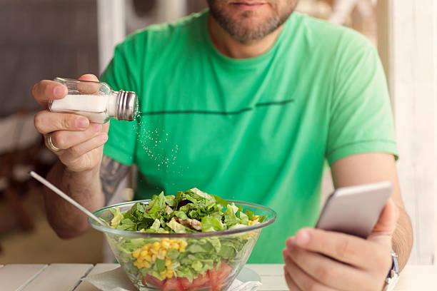 mann das salzen speisen und er ein smartphone benutzt - speisesalz stock-fotos und bilder