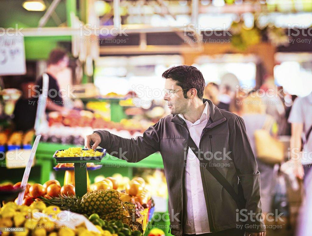 Man sampling pineapples at the market royalty-free stock photo