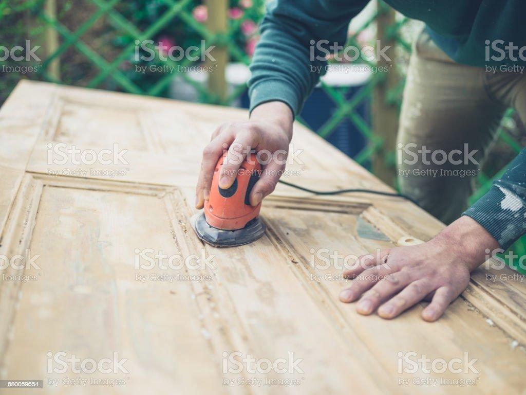 Man sanding old door stock photo