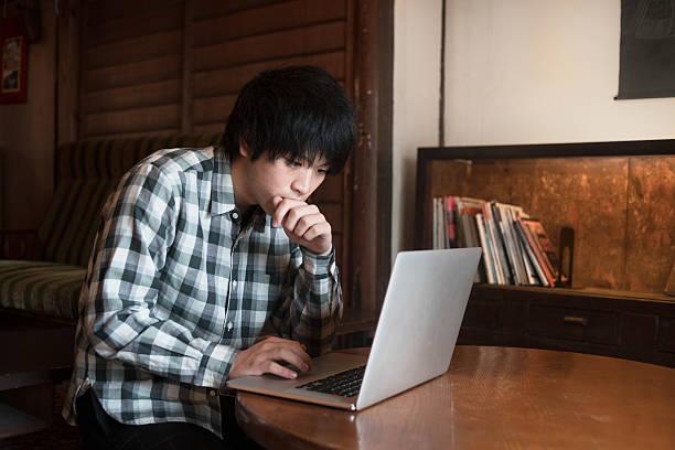 男 土 を使用しているコンピュータのカフェ - 大学生 パソコン 日本 ストックフォトと画像
