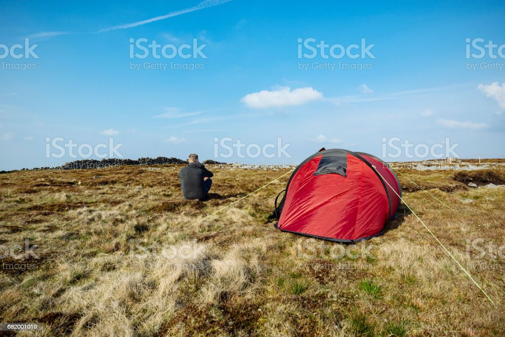 Man sat next to red tent in remote location. stock photo