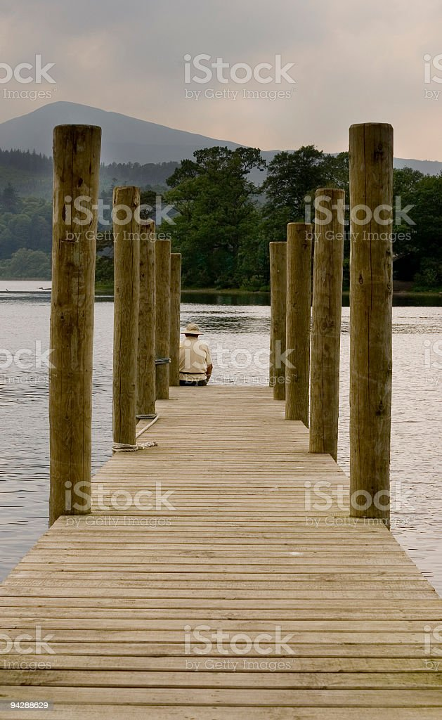 Man sat on wooden jetty. royalty-free stock photo