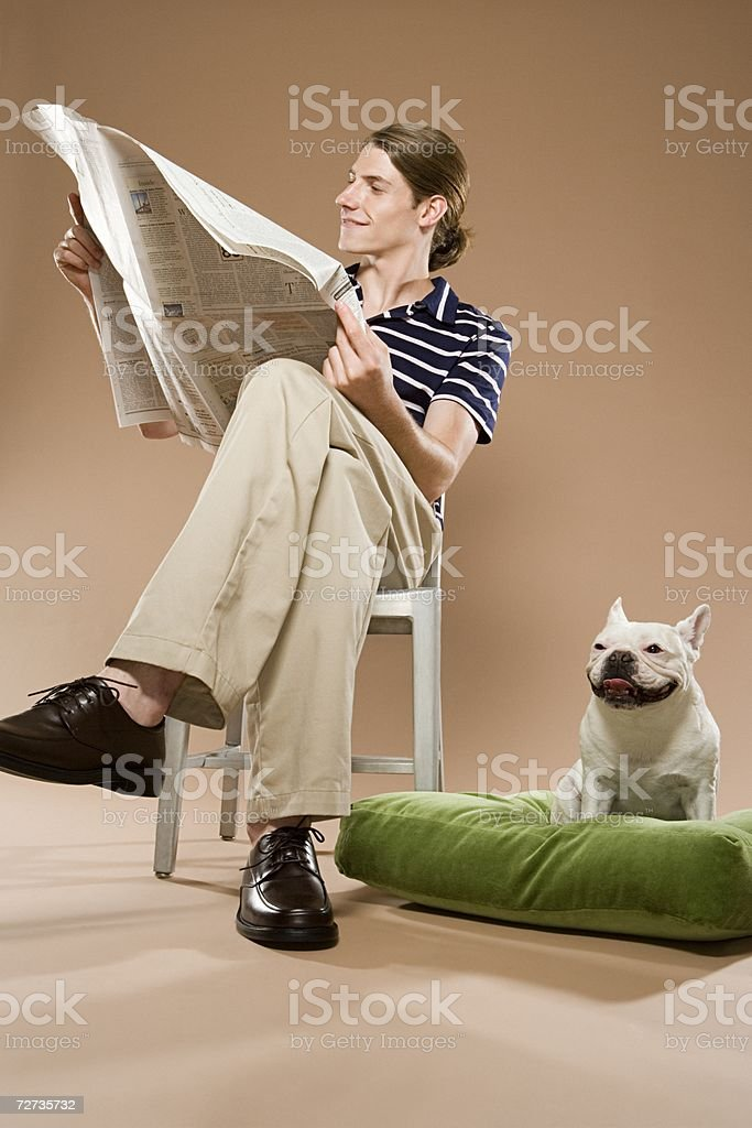 Man sat reading paper with dog royalty-free stock photo