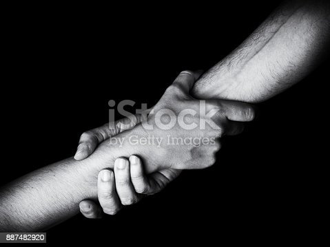 istock Man saving, rescuing and helping woman by holding or griping the forearm. 887482920