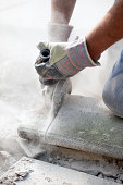 detail on man's hands sawing stone with grinder