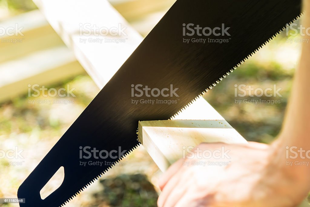 Man sawing a wood board outdoors stock photo