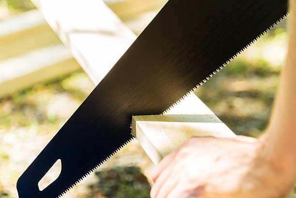 man sawing a wood board outdoors - fuchsschwanz stock-fotos und bilder