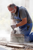 Hard working bearded craftsman with safety glasses, blue workwear and gloves sawing stone with grinder