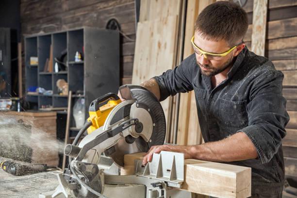 mann-sägen mit einer kreissäge - werkzeugbank stock-fotos und bilder