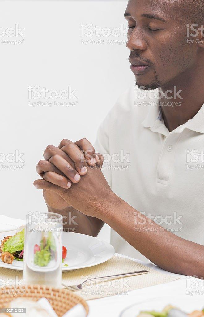 Man saying grace before having dinner stock photo