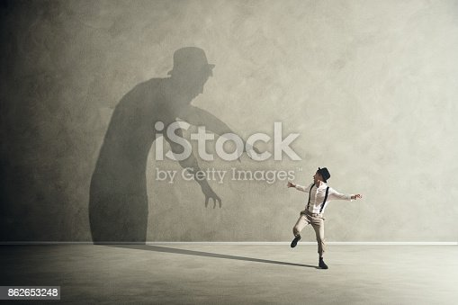 istock Man scared by his demon shadow 862653248