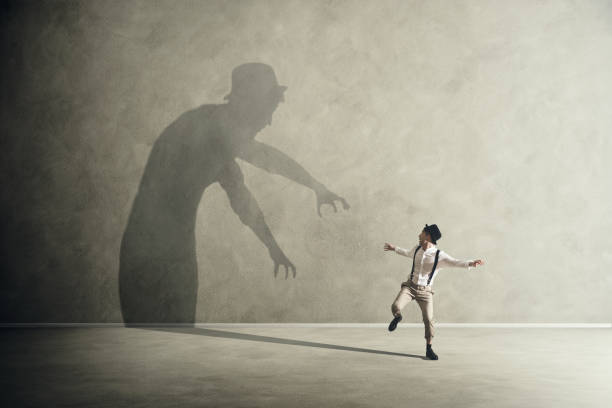 Man scared by his demon shadow stock photo