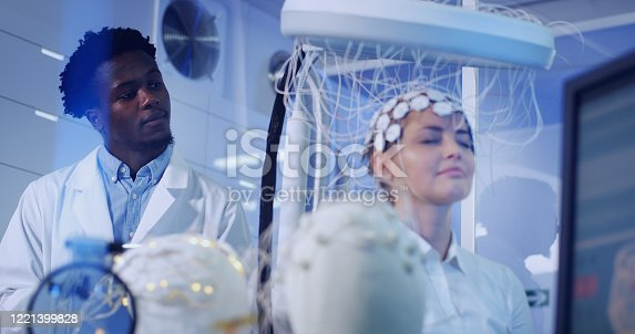 Scientists examines headset in modern Neurological Research Laboratory.